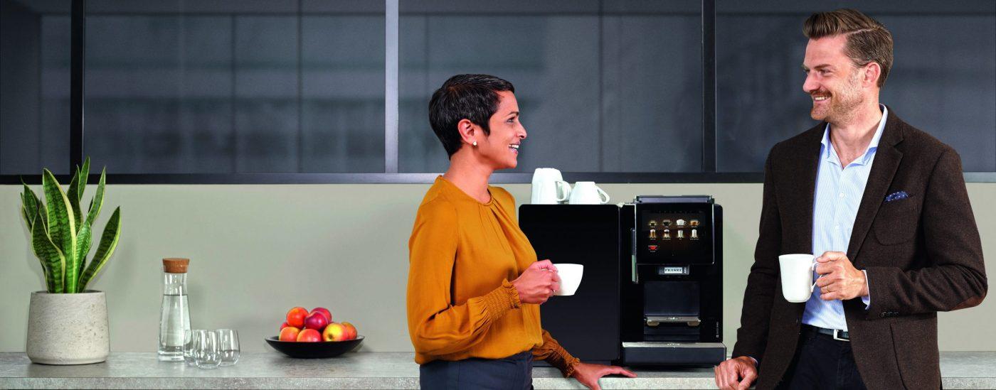 Mann og dame som står foran Franke a300 kaffemaskin og drikker kaffe