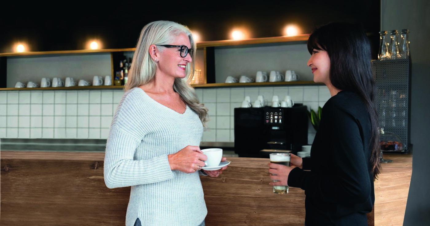 to damer på et kontor som prater ved kaffemaskiner og drikker kaffe på jobb