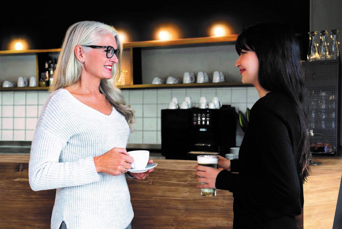 to damer som drikker kaffe på jobb og prater ved kaffemaskiner og drikker kaffe på jobb